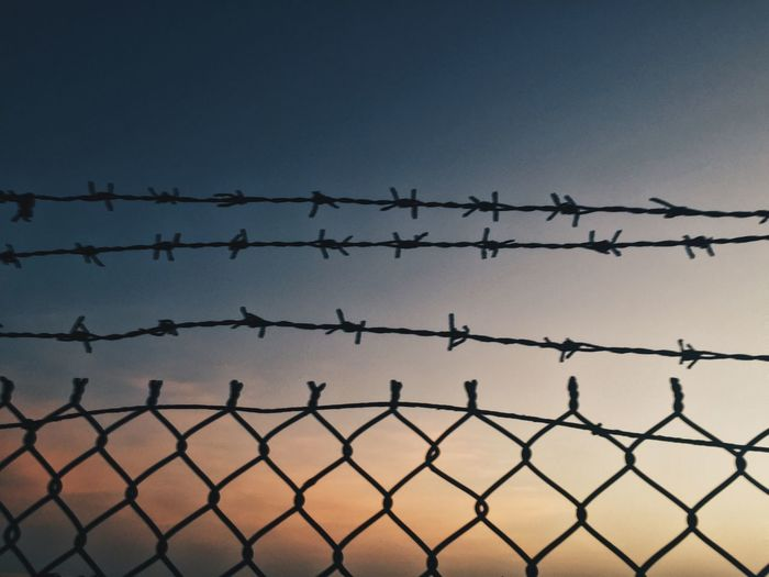 Low angle view of chainlink fence against clear sky