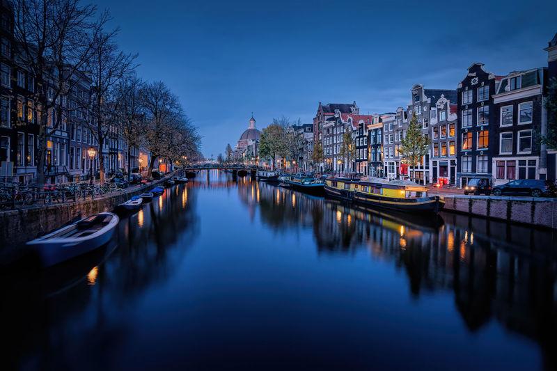 Canal amidst illuminated city buildings against sky at dusk