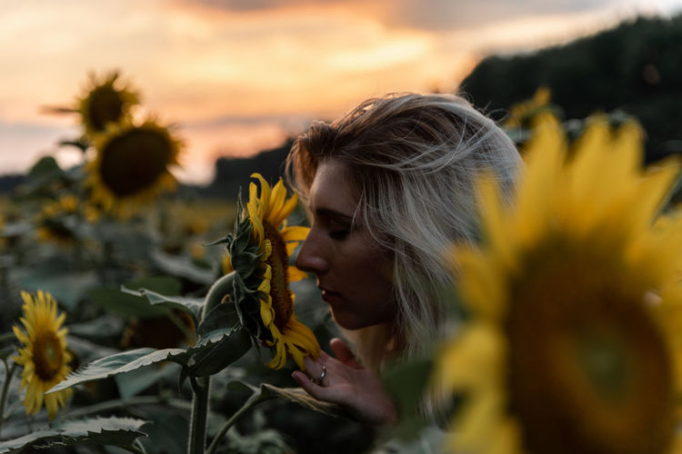 Close-up of woman smelling sunflower