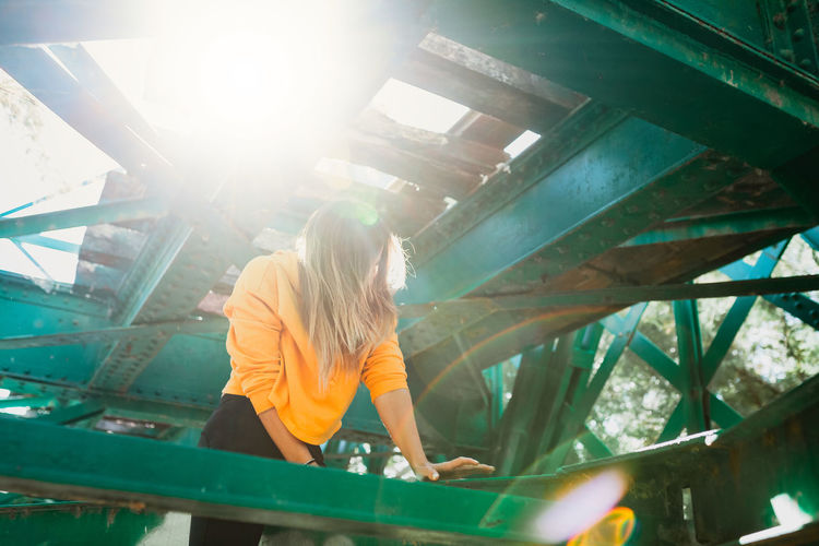 Low angle view of woman standing by built structure