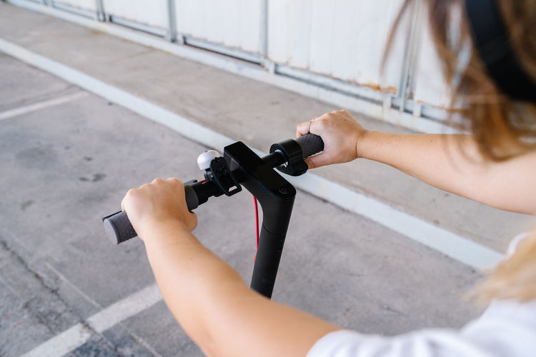 High angle view of woman holding bicycle on street