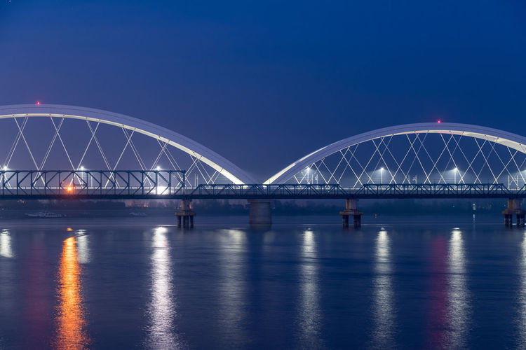 Illuminated Bridge Over River Against Blue Sky At Night
