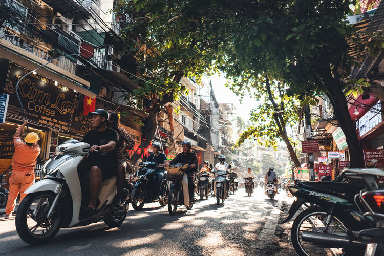People riding motorcycle on street against buildings in city
