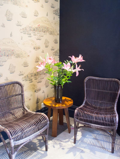 Vase of flowers and two cane chairs in the corner Cane Chairs Chair Flower Flower Display Furniture Home Interior Indoors  Seat Table