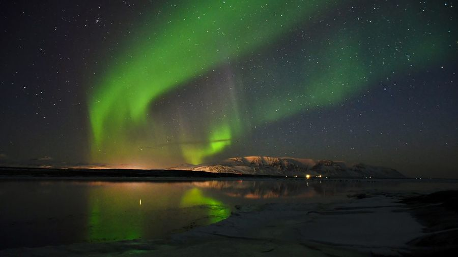 Scenic view of the northern lights reflected in the waters of the icelandic fjord