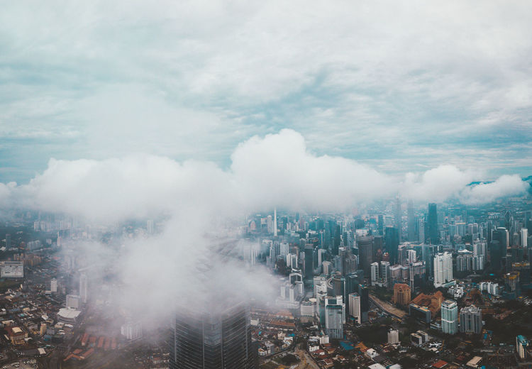 High angle view of modern buildings in city against sky under low clouds