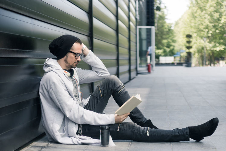 It is always right time for a good book. Campus EyeEmNewHere Learning Man Reading Student Book Building Exterior Casual Clothing Caucasian Ethnicity City Enjoyment Eyeglasses  Literature Male Men Novel Outdoors Reading A Book Resting Studying University Student Knowledge Adult Student