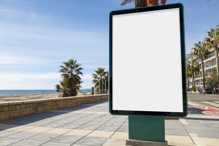 Blank advertisement mock up in the street Billboard Advertising Poster Blank White Mock Up Mockup Mock Up Empty Outdoor Sea Water Blue Sky Promenade Palm Sidewalk Media Board Marketing Display Information Message Sign City Advertisement Outside Commercial Roadside Street Urban Tree Public Panel Placard Ad Footpath Pathway Maritime Beach Sand Surfer Surf Paddle Surf Paddle Advertising Branding