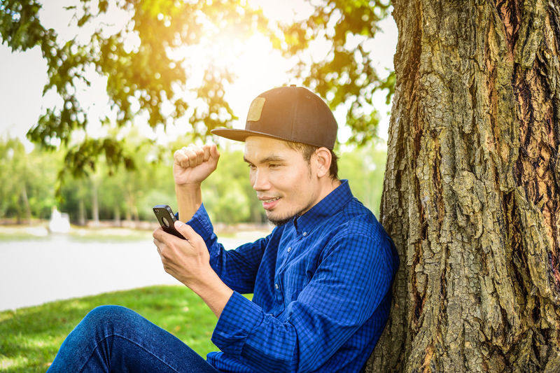 Man With Clenched Fist Looking At Mobile Phone While Sitting By Tree