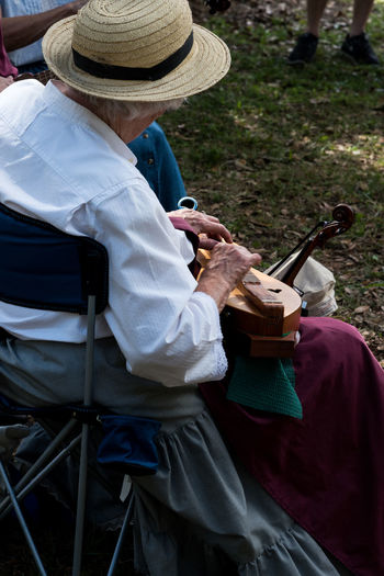 Woman playing musical instrument while sitting on chair