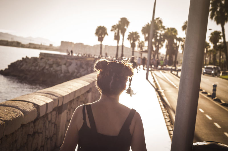 Rear view of woman walking on footpath by sea during sunny day