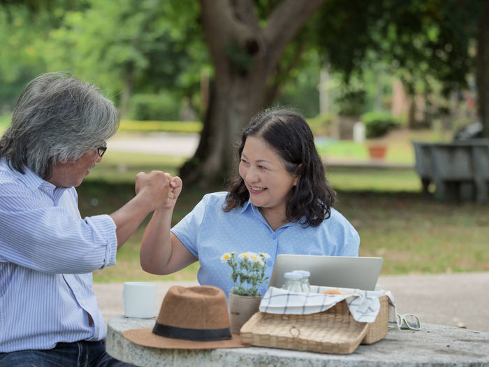 Couple doing fist bump while sitting at table in park