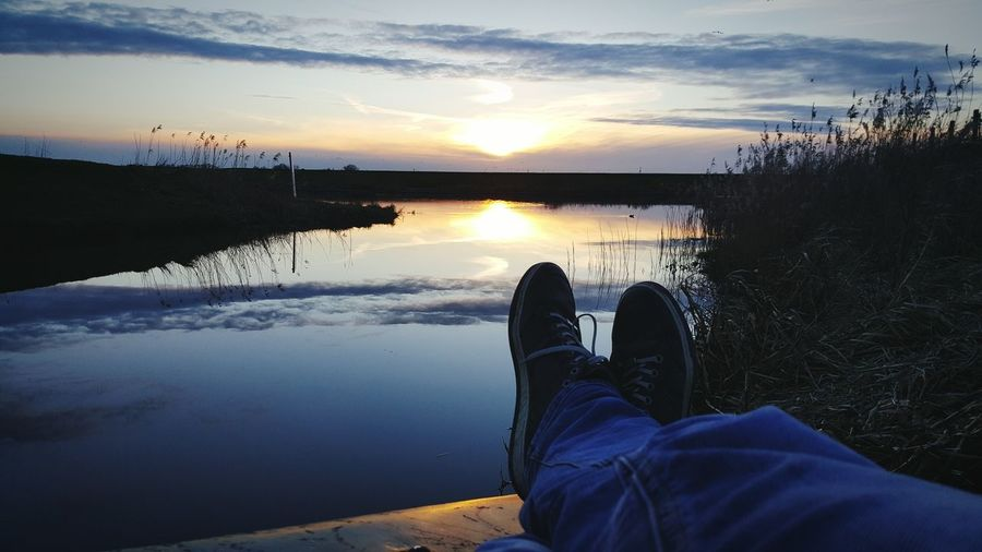 Low section of man relaxing on pier by lake at sunset