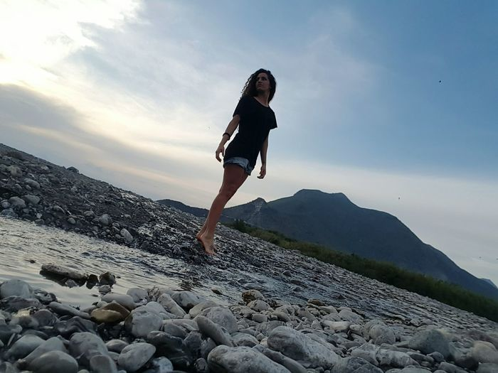 Low angle view of woman standing on pebbles by stream flowing against sky