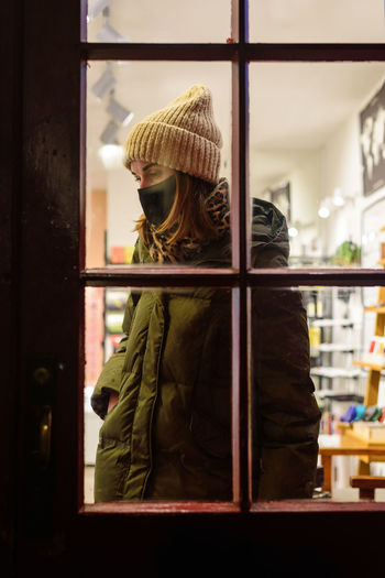 Rear view of woman standing by window in store