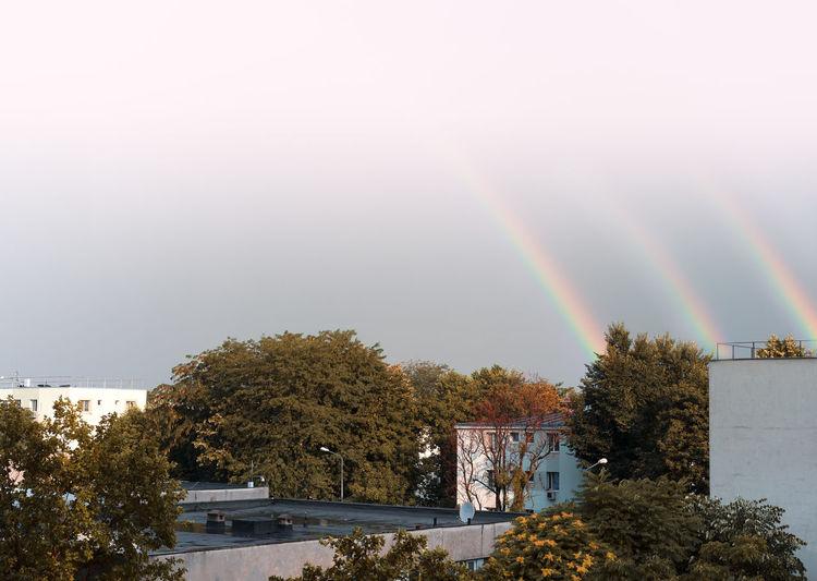 Triple rainbow over buildings in city against sky