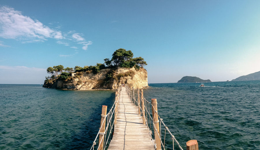 Footbridge over sea against sky