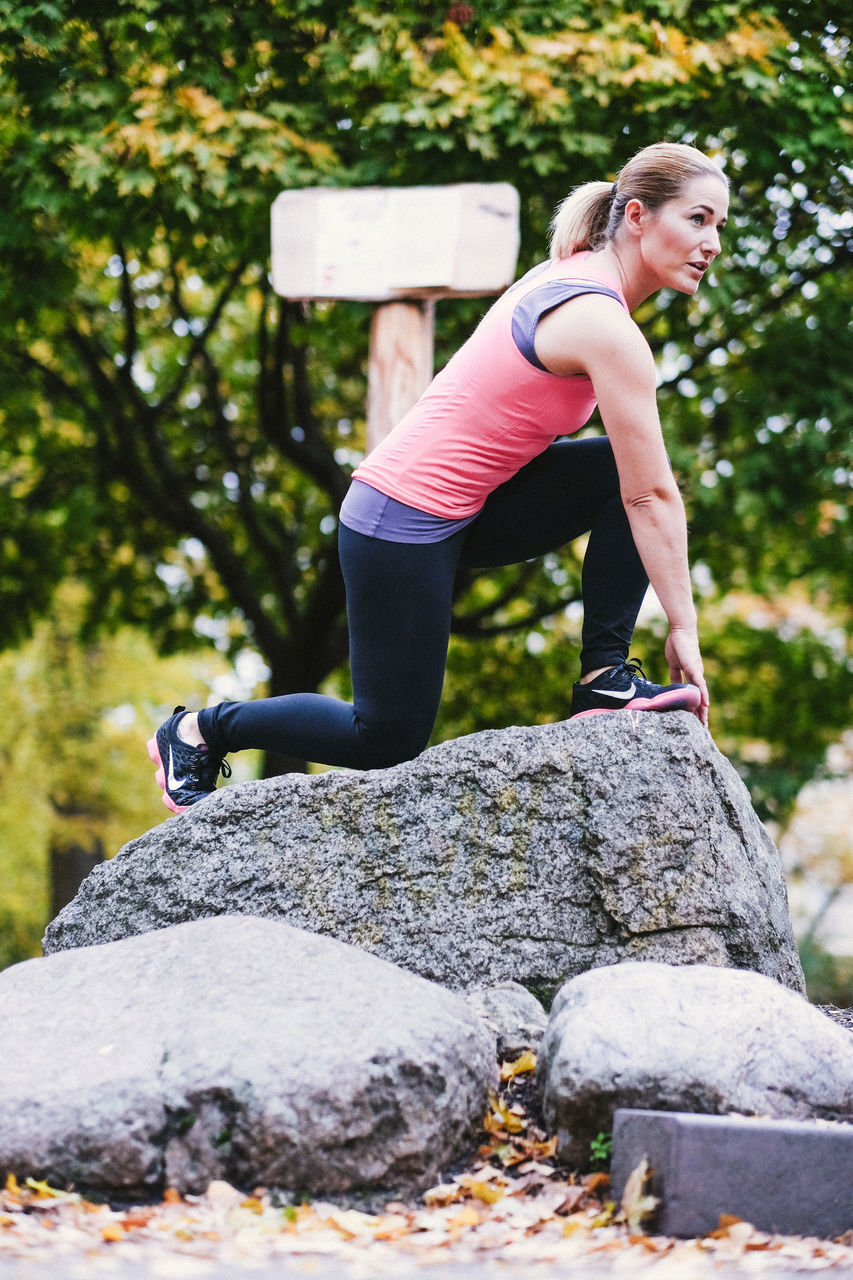 exercising, lifestyles, one person, sports clothing, healthy lifestyle, rock - object, full length, balance, day, leisure activity, young women, outdoors, women, real people, strength, young adult, sport, side view, flexibility, one woman only, tree, nature, adult, adults only, people