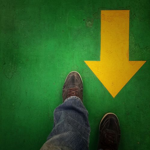 Low section of man standing on green sign