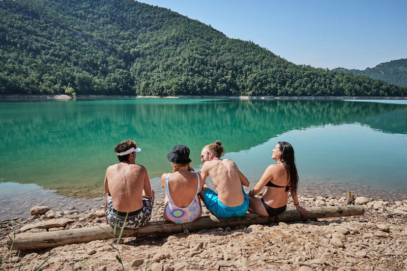 Rear view of people sitting on lake against mountain