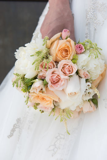 Midsection of bride holding bouquet