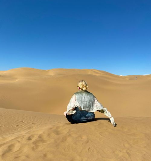 Rear view of woman with scarf on desert against clear sky