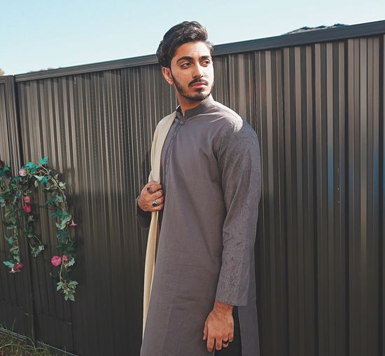 Fashionable young man wearing traditional clothes standing against wall