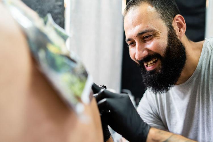 Artist tattooing on customer body