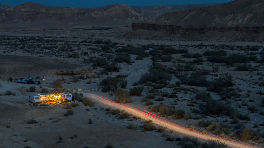 High angle view of light trails on desert road at night