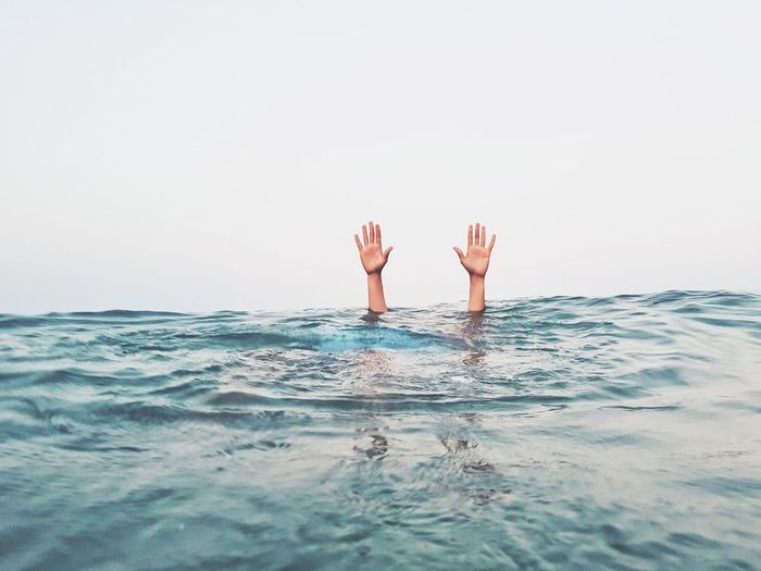 Cropped hands of person emerging from sea against clear sky