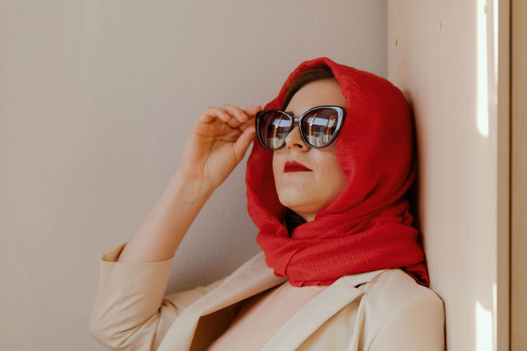 Portrait of woman wearing sunglasses sitting at home