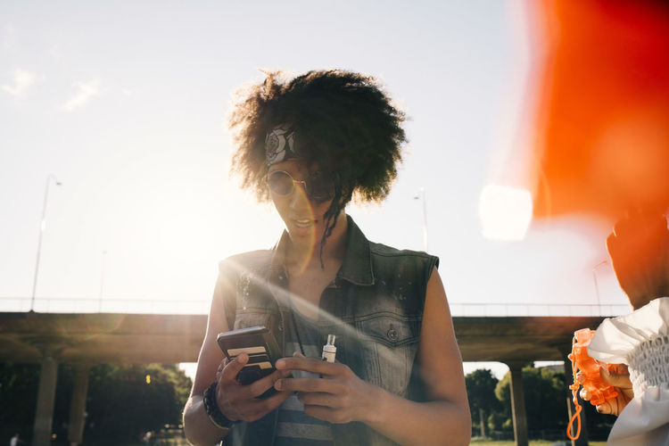 Young woman using mobile phone against sky