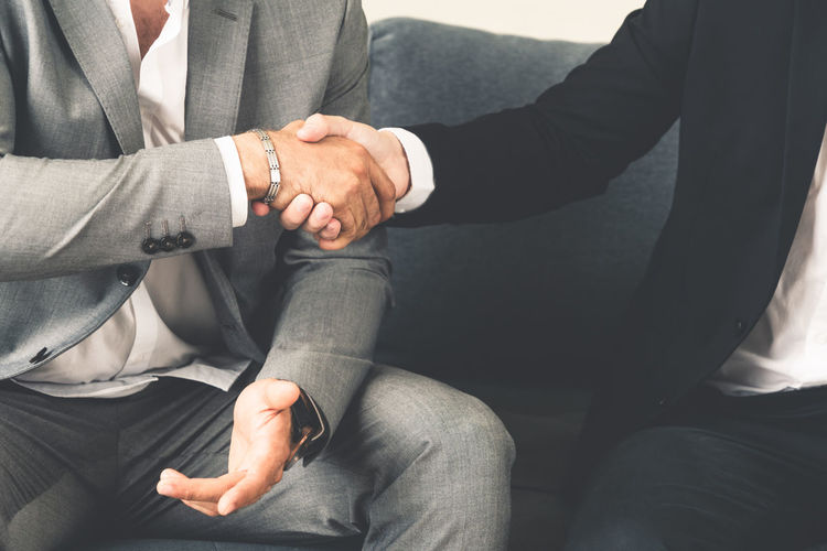 Midsection of business people shaking hand while sitting on sofa at office