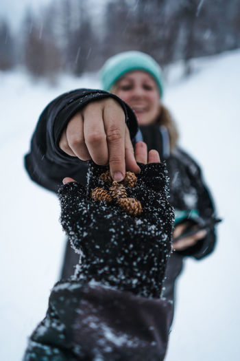 Pine cones laying in hand from first person view Winter Snow Cones Cone Pine Tree Pine Cones Forest Tree Hand Body Part Blurry Background First Person View Mountain Snowing Outdoors Authentic Moments