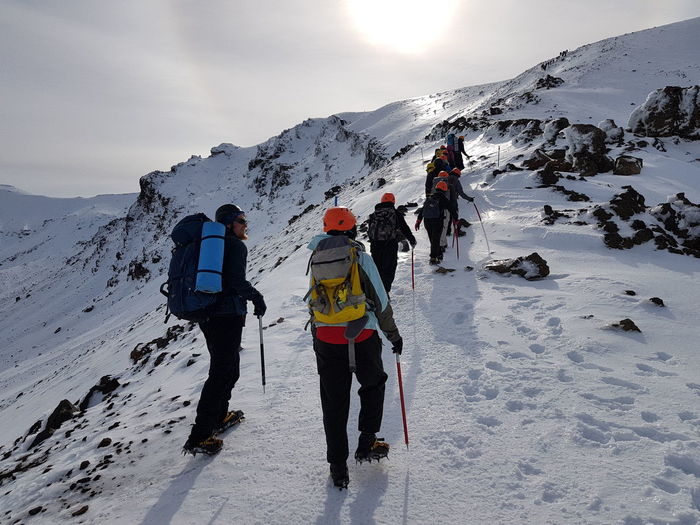 Rear view of people on snowcapped mountain against sky