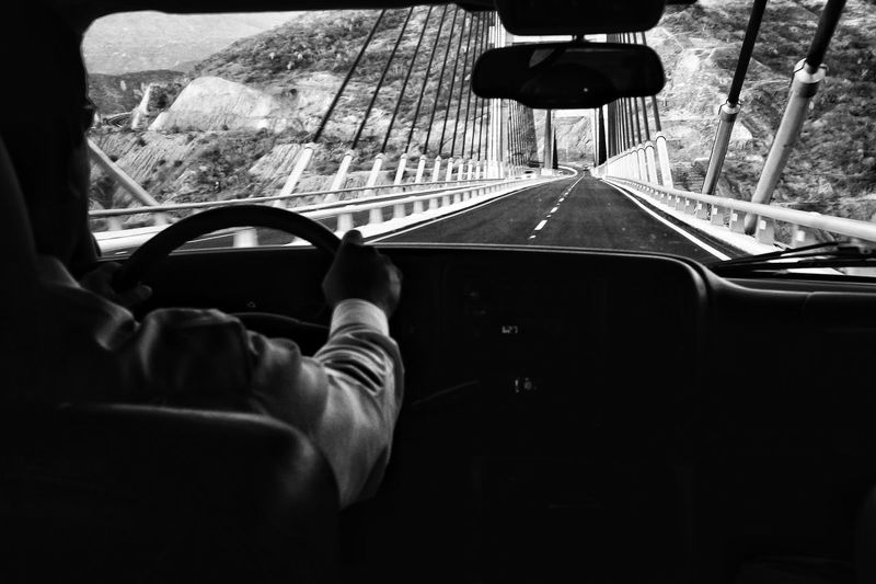 Man driving car on suspension bridge