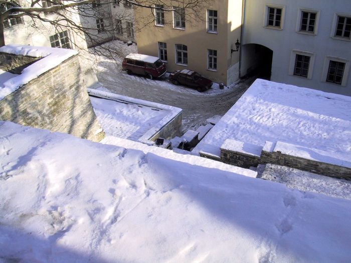 High angle view of snow covered houses by buildings