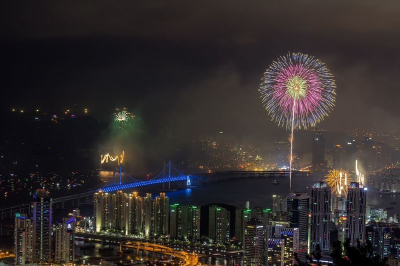 Firework display over city by gwangandaegyo at night