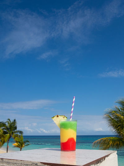 Multicolored cocktail on table with Blue Sky Drinking Straw Glass Cocktail Caribbean Sky Blue Relaxing Sea Holiday Vacation Red Yellow Green Blue Sky Pineapple Alchohol