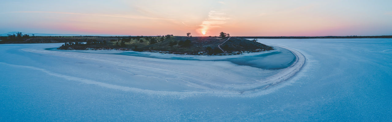 Aerial view frozen lake against sky during sunset