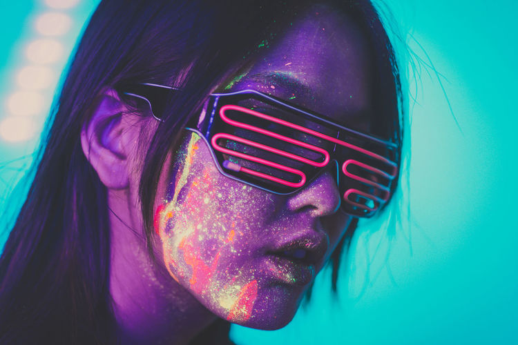 Beautiful young woman with face paint wearing eyewear