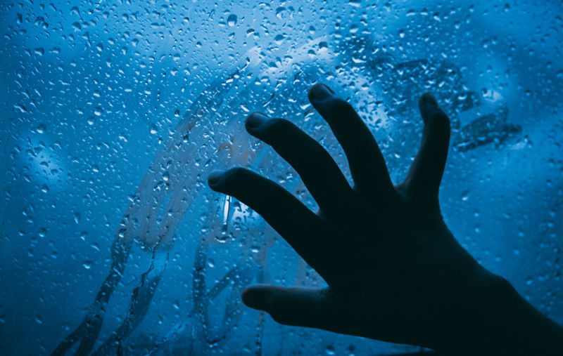 Close-up of hand touching wet glass window at night