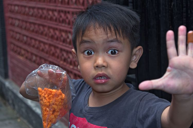 Close-up portrait of shocked boy holding snacks in plastic