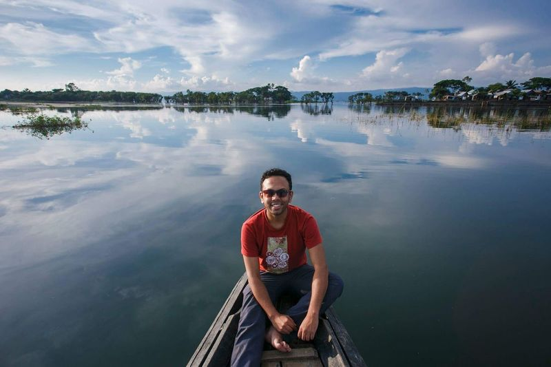 Portrait of man sitting in boat on lake against sky