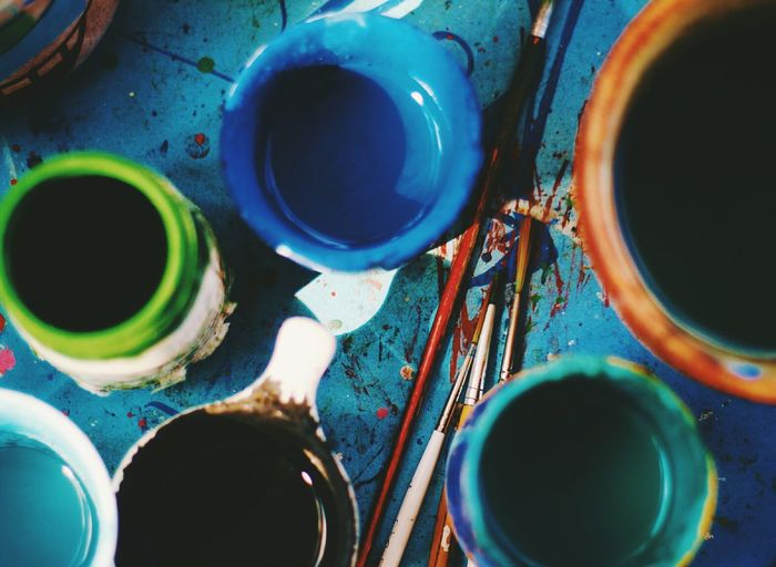 High angle view of color bottles with paintbrush on table