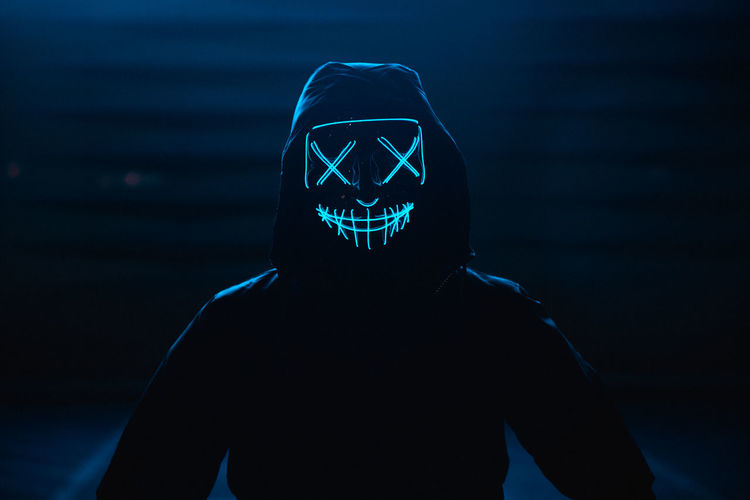 Portrait of man wearing glowing mask standing against black background