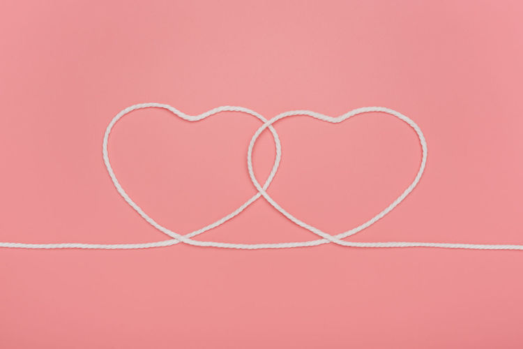 Directly above shot of heart shape on pink background