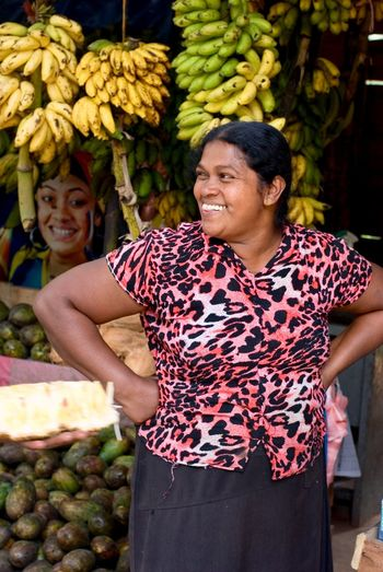 Smiling young woman with fruits at market stall
