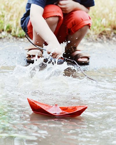 Low section of boy with paper boat splashing water at lakeshore