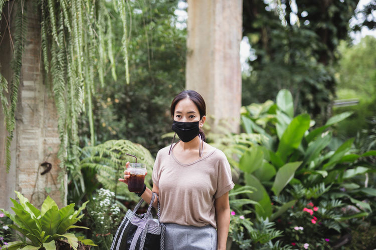 Portrait of woman in protective mask standing against plants